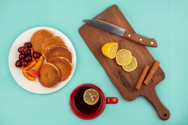 Top view of pancakes with cherries and apricot slices in plate and cup of coffee with lemon slices and cinnamon with knife on cutting board on blue background