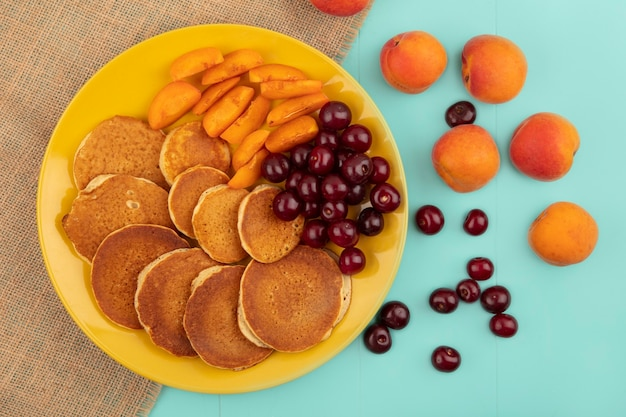 Top view of pancakes with cherries and apricot slices in plate on sackcloth and apricots cherries on blue background