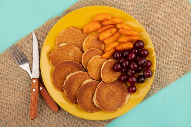 Top view of pancakes with cherries and apricot slices in plate with fork and knife on sackcloth on blue background