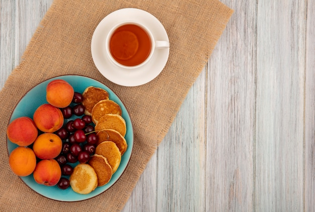 Top view of pancakes with cherries and apricots in plate and cup of tea on saucer on sackcloth and wooden background with copy space