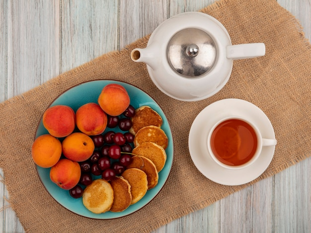 Top view of pancakes with cherries and apricots in plate and cup of tea with teapot on sackcloth and wooden background