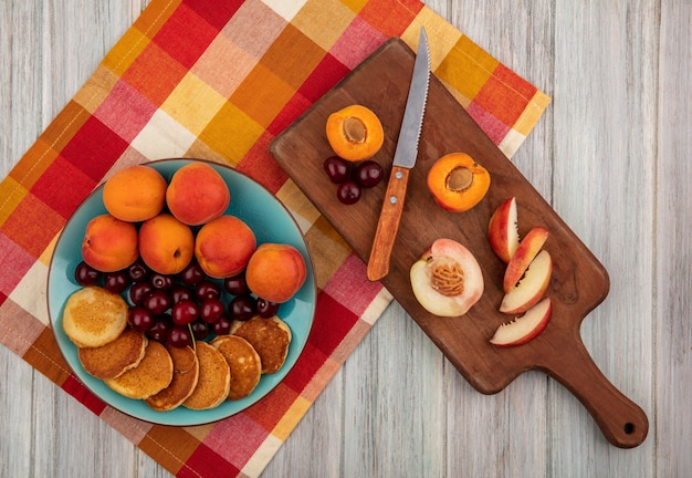 Top view of pancakes with cherries and apricots in plate and cut apricot peach with knife on cutting board on plaid cloth on wooden background