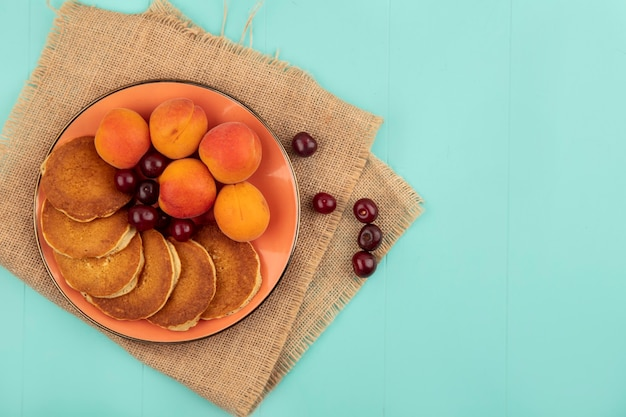 Top view of pancakes with cherries and apricots in plate on sackcloth on blue background with copy space