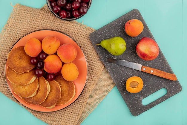 Top view of pancakes with cherries and apricots in plate on sackcloth with bowl of cherries and pear peach apricot with knife on cutting board on blue background