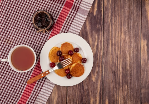 Top view of pancakes with cherries and fork in plate and cup of tea with strawberry jam on plaid cloth on wooden background with copy space