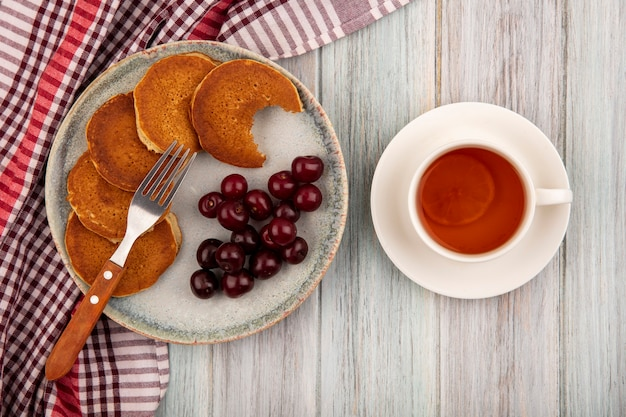 Top view of pancakes with cherries and fork in plate on plaid cloth and cup of tea on wooden background