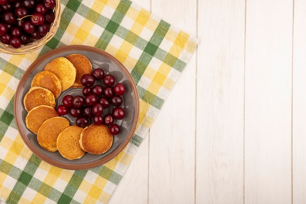 Top view of pancakes with cherries in plate and basket of cherries on plaid cloth and wooden background with copy space
