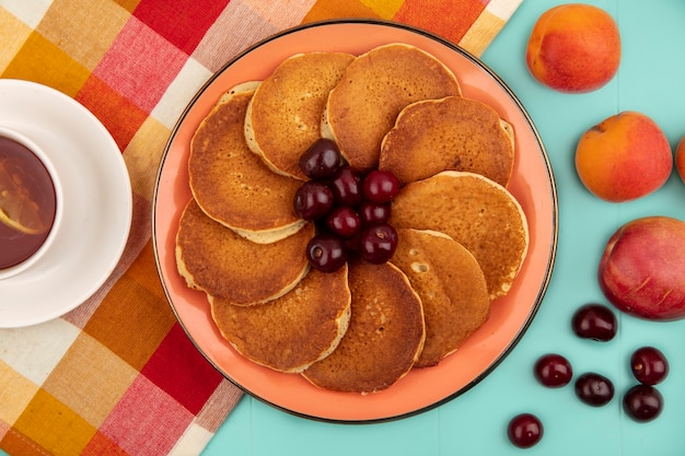 Top view of pancakes with cherries in plate and cup of tea on plaid cloth with apricots on blue background