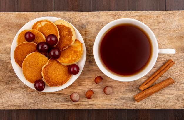 Top view of pancakes with cherries in plate and cup of tea with cinnamon and nuts on cutting board on wooden background