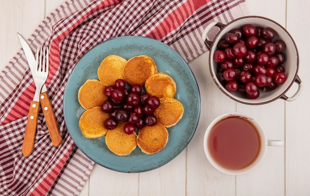 Top view of pancakes with cherries in plate and fork knife on plaid cloth and bowl of cherries with cup of tea on wooden background