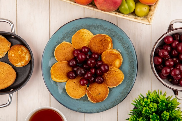 Top view of pancakes with cherries in plate and pan of pancakes with bowl of cherries and fruits with tea on wooden background