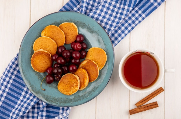 Top view of pancakes with cherries in plate on plaid cloth and cup of tea with cinnamon on wooden background