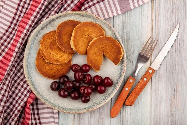 Vista dall'alto di frittelle con ciliegie nel piatto su panno plaid e coltello forchetta su fondo in legno