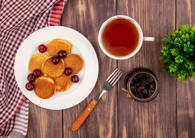 Top view of pancakes with cherries in plate on plaid cloth with cup of tea fork and strawberry jam on wooden background