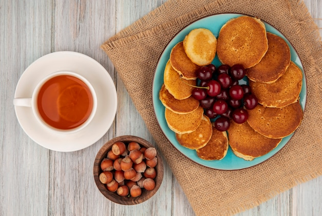 Top view of pancakes with cherries in plate on sackcloth and cup of tea with bowl of nuts on wooden background