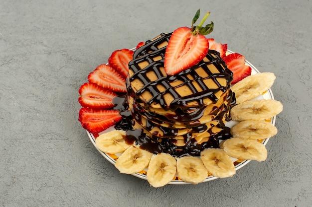 Frittelle vista dall'alto con cioccolato e frutta fresca sul pavimento grigio