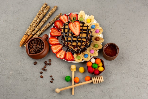 Top view pancakes with chocolate red sliced strawberries and bananas along with candy sticks and colorful candies on the grey floor