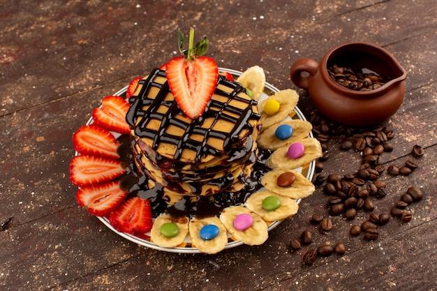 新鮮なフルーツとチョコレートの茶色の木の床で平面図パンケーキ