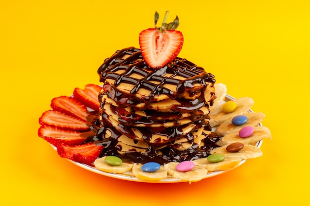 Top view pancakes with fruits and chocolate on the yellow floor