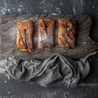 Вид сверху блины с мясом с шоколадным сиропом и сахарной пудрой и тряпкой в разделочной доске