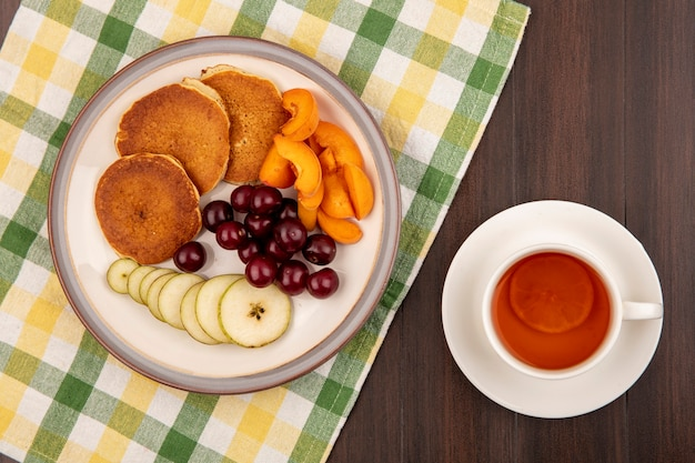 Top view of pancakes with pear and apricot slices and cherries in plate on plaid cloth with cup of tea on wooden background