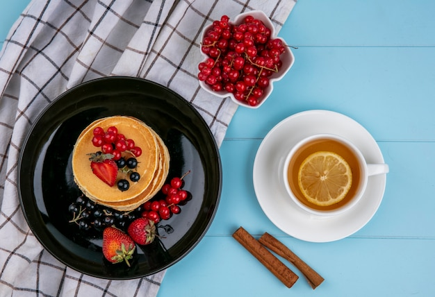Top view of pancakes with red and black currants and strawberries on a black plate with a cup of tea on a blue surface