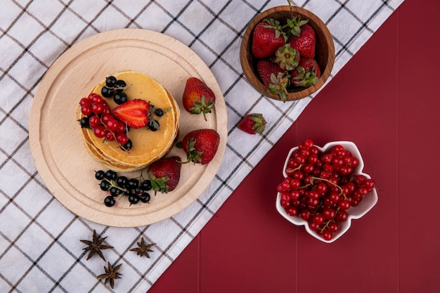 Top view pancakes with red and black currants and strawberries on a towel on a red background