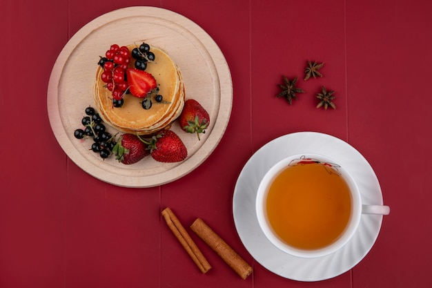 Top view pancakes with red and black currants and strawberries on a tray with a cup of tea and cinnamon on a red background