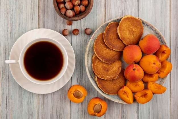 Top view of pancakes with whole and sliced apricots in plate and cup of tea with bowl of nuts on wooden background