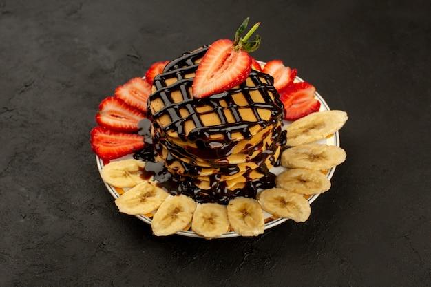 Vista dall'alto frittelle deliziose con frutta e cioccolato sul pavimento scuro