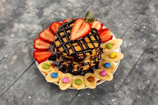 Vista dall'alto pancake deliziosi con fragole rosse a fette e banane all'interno della piastra sul grigio
