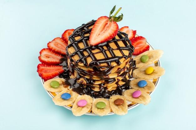 Vista dall'alto frittelle deliziose con fragole rosse a fette e banane all'interno del piatto bianco sul blu ghiaccio