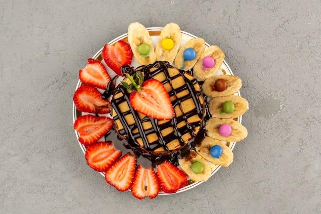 Вид сверху блины вкусные сладкие вкусные со свежими фруктами и шоколадом на сером