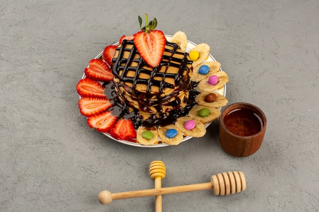 グレーの床にフルーツとチョコレートのおいしいパンケーキ