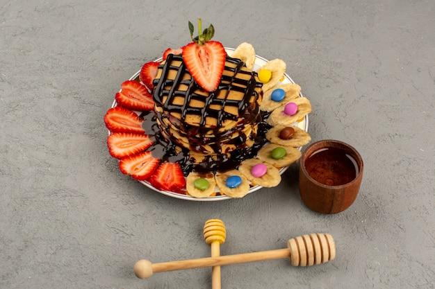 Pancakes vista dall'alto buonissimo con frutta e cioccolato sul pavimento grigio