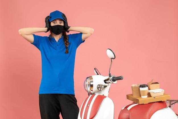 Vista dall'alto della ragazza del corriere in preda al panico in maschera medica in piedi accanto alla moto con una torta di caffè su di essa su sfondo color pesca pastello