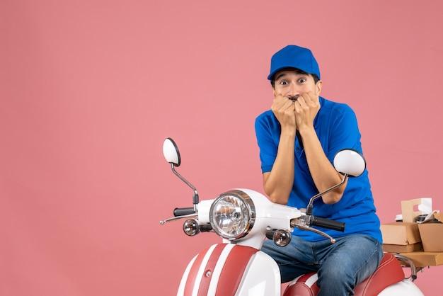 Vista dall'alto del corriere in preda al panico che indossa un cappello seduto su uno scooter che consegna ordini su sfondo color pesca pastello