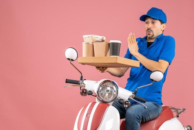 Vista dall'alto di un corriere in preda al panico che indossa un cappello seduto su uno scooter su sfondo color pesca pastello