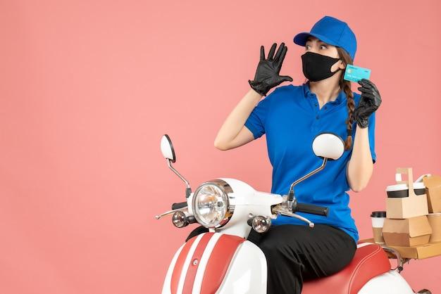 Vista dall'alto della donna del corriere in preda al panico che indossa maschera medica e guanti seduta su scooter in possesso di carta di credito che consegna ordini su sfondo color pesca pastello