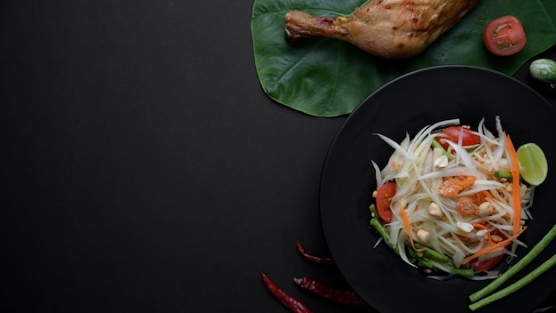 Top view of papaya salad on black plate, chicken grill on green taro a