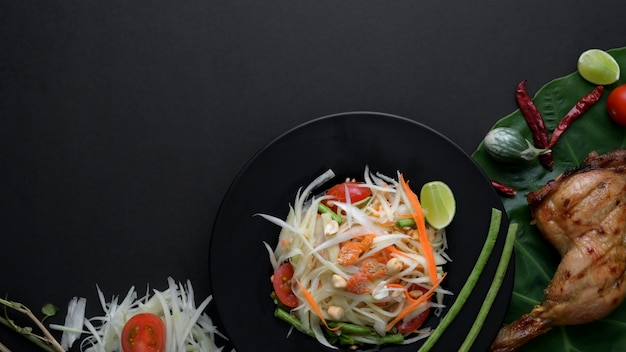 Top view of papaya salad, chicken grill, ingredients on black plate