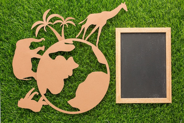Top view of paper animals and planet with blackboard on grass for animal day