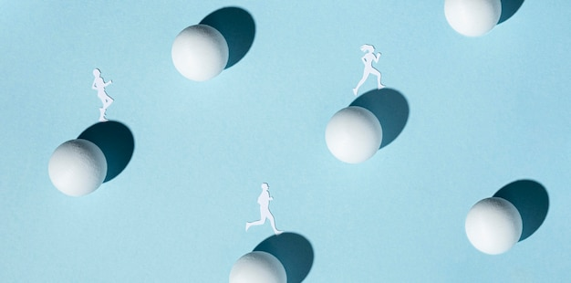 Top view of paper athletes with ping pong balls