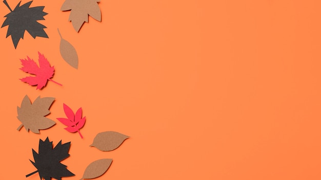 Top view paper autumn leaves on orange background with copy space