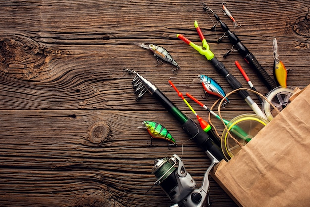 Top view of paper bag with fishing essentials and copy space