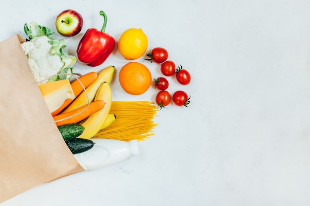 Top view of paper bag with fruits, vegetables, spaghetti, cheese, milk on white background