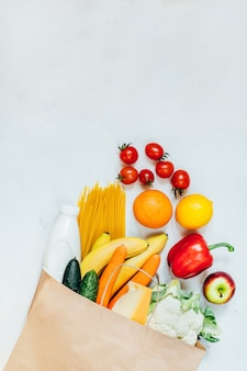 Top view of paper bag with fruits, vegetables, spaghetti, cheese, milk on white surface