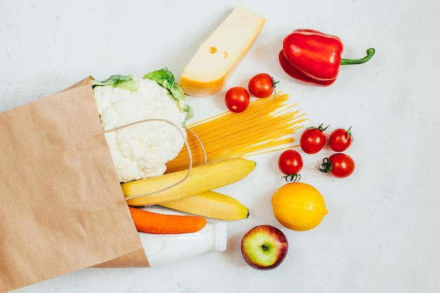 Top view of paper bag with fruits, vegetables, spaghetti, cheese, milk on white