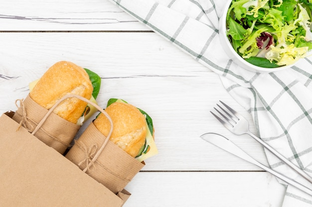 Top view of paper bag with two sandwiches inside and salad