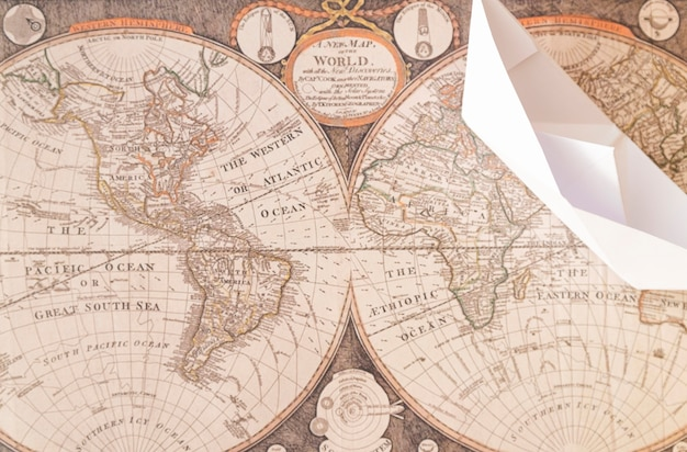 Top view paper boat on old world map